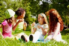 portrait of cute girls having fun on grass in park - stock photo