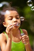 portrait of cute girl blowing soap bubbles - stock photo