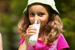Portrait of cute girl drinking kefir outdoors Stock Photos