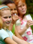portrait of cute girl looking at camera with her friends drinking kefir on backg - stock photo