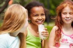 Portrait of cute girl drinking kefir outdoors with her friends near by Stock Photos