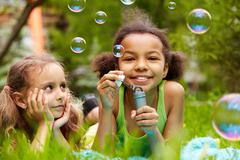 Portrait of cute girl blowing soap bubbles with her friend near by Stock Photos
