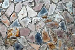 Masonry wall with irregular shaped stones Stock Photos
