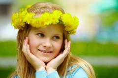 close-up of cute girl with dandelion wreath posing on summer day - stock photo