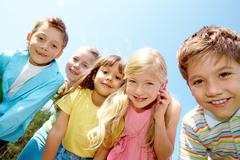 portrait of smiling children looking at camera on background of blue sky - stock photo