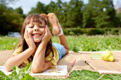 portrait of little smiling girl lying on grass with book - stock photo