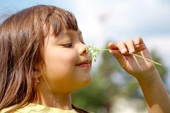 portrait of little girl enjoying smell of flower - stock photo