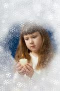 Image of youthful girl with candle in hands looking at it behind window Stock Photos