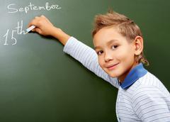 portrait of smart schoolchild by the blackboard looking at camera - stock photo
