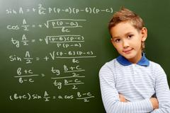 portrait of smart schoolchild by the blackboard with sums on it looking at camer - stock photo