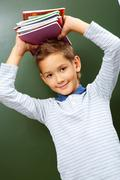 Portrait of smart lad with copybooks on head looking at camera Stock Photos
