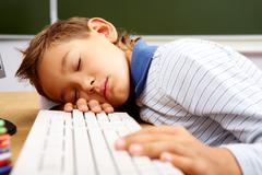 Portrait of cute lad sleeping with his head on computer keyboard in classroom Stock Photos