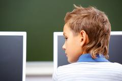 Portrait of cute lad in front of monitor in classroom Stock Photos