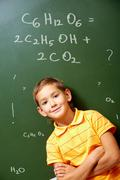portrait of smart schoolchild by the blackboard and looking at camera - stock photo