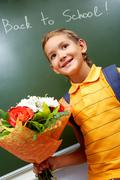 portrait of smart schoolchild with bunch of flowers by the blackboard - stock photo