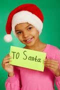 portrait of happy girl in santa cap holding envelope with note 'to santa' - stock photo