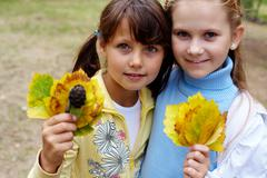 portrait of two girls holding yellow leaves and looking at camera with smiles - stock photo
