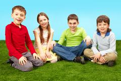 image of happy boys and girls having rest on green grass - stock photo