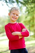 Stock Photo of portrait of happy lad crossing arms and looking at camera with smile