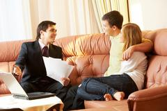 Portrait of a businessman with papers explaining something to young couple Stock Photos
