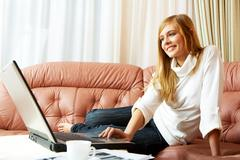 Image of pretty girl in home clothes looking at laptop monitor while sitting on Stock Photos