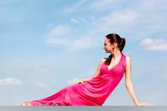 portrait of woman in pink dress sitting after dancing - stock photo