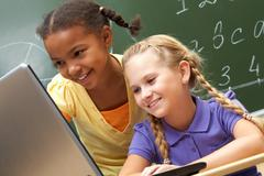 portrait of two schoolgirls looking at the laptop during lesson - stock photo