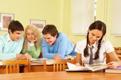 Portrait of smart students discussing book with smart girl at foreground Stock Photos