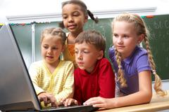 Portrait of smart schoolgirls and schoolboy looking at the laptop with blackboar Stock Photos
