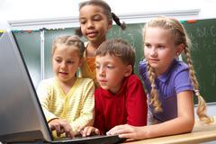 portrait of smart schoolgirls and schoolboy looking at the laptop with blackboar - stock photo