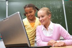portrait of pupil and teacher looking at the laptop in classroom - stock photo