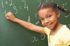 portrait of smart schoolchild standing at blackboard and looking at camera - stock photo