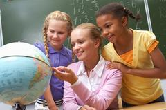 Portrait of pupils looking at globe being pointed at by lecturer during lesson Stock Photos