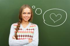 portrait of pretty girl by the blackboard thinking of falling in love - stock photo