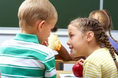 Portrait of schoolchildren sitting in classroom and chatting at lesson Stock Photos