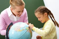 portrait of cute girl and teacher looking at globe during lesson - stock photo