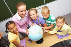 portrait of pupils and teacher looking at camera with globe on table during geog - stock photo