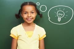 Portrait of smart girl by the blackboard thinking of light idea and looking at c Stock Photos