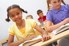 portrait of smart pupils sitting in the classroom and reading - stock photo