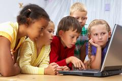 Stock Photo of portrait of smart schoolgirls and schoolboys looking at the laptop