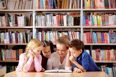 portrait of pupils and teacher looking at page of interesting book in library - stock photo