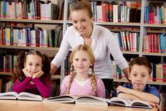 Portrait of pupils and teacher looking at camera with smiles in library Stock Photos