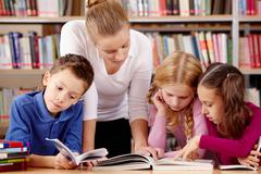 Portrait of pupils and teacher reading interesting book in library Stock Photos