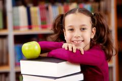 Stock Photo of portrait of pretty schoolgirl looking at camera with green apple on top of book