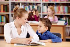 Portrait of schoolboy and teacher reading and discussing interesting book Stock Photos