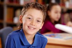 portrait of smart lad looking at camera during lesson - stock photo