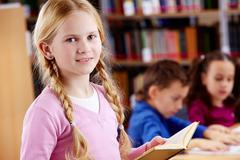 Portrait of happy schoolgirl with open book looking at camera in library Stock Photos