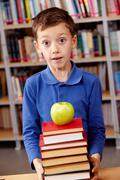 Stock Photo of portrait of amazed lad with green apple on top of book heap near by