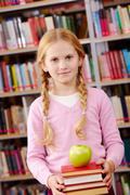 Portrait of pretty schoolgirl looking at camera with green apple on top of book Stock Photos