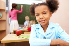 Portrait of smart schoolgirl smiling at camera during lesson in classroom Stock Photos
